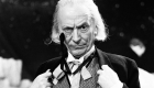 William Hartnell as The FIrst Doctor with his hands on his lapels and wearing a monocle