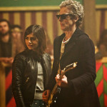 The 12th Doctor holding an electric guitar next to Clara in The Magician's Apprentice
